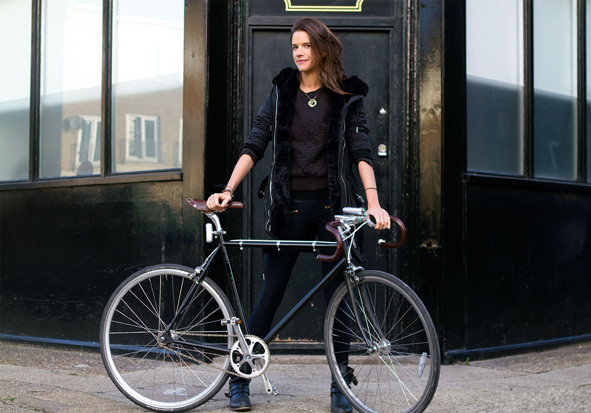 Inventor Emily Brooke standing with a bike