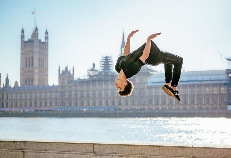 Parkour athlete does a backflip on a bridge in London next to the Thames