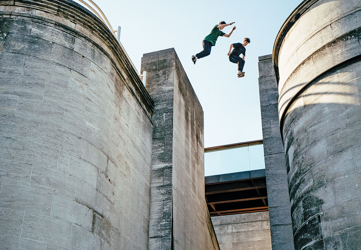 Two parkour athletes jump between buildings in London