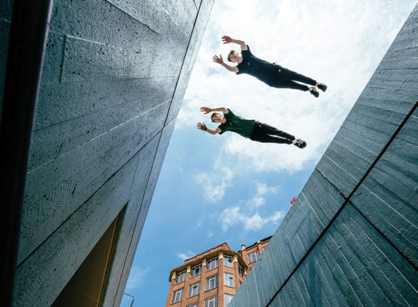 Two Parkour Athletes dive across a building